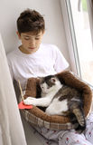 Muchacho del adolescente con el gato en la cama que juega cerca encima de la foto Fotos de archivo libres de regalías