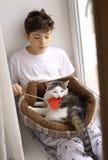 Muchacho del adolescente con el gato en la cama que juega cerca encima de la foto Fotos de archivo