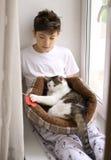 Muchacho del adolescente con el gato en la cama que juega cerca encima de la foto Foto de archivo libre de regalías
