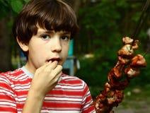 Muchacho del adolescente con el shashlik asado de la carne de la carne de vaca en el pincho del hierro del braiser Fotografía de archivo