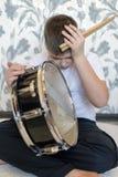 Muchacho del adolescente con el tambor que lleva a cabo su cabeza Foto de archivo