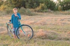 Muchacho del adolescente con la bici azul en campo de granja Imagenes de archivo