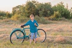 Muchacho del adolescente con la bici retra en campo de granja Fotos de archivo libres de regalías