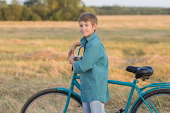 Muchacho del adolescente con la bicicleta en campo de granja de la puesta del sol Fotos de archivo