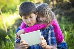 Muchacho del adolescente con la tableta y su hermana más joven, al aire libre armonía Fotos de archivo