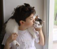 Muchacho del adolescente con mirada que se besa del gato fuera de la ventana Fotos de archivo