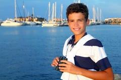 Muchacho del adolescente de los prismáticos en puerto deportivo del barco Imágenes de archivo libres de regalías