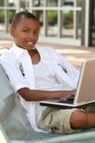 Muchacho del adolescente del afroamericano en el ordenador portátil Imagen de archivo