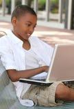 Muchacho del adolescente del afroamericano en el ordenador portátil Fotos de archivo