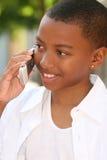 Muchacho del adolescente del afroamericano en el teléfono celular Foto de archivo libre de regalías