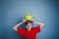 Muchacho del adolescente doce años en la camisa roja que sostiene a Imagen de archivo