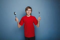 Muchacho del adolescente doce años en una camisa roja que sostiene a Imagen de archivo libre de regalías
