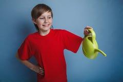Muchacho del adolescente doce años en una camisa roja que sostiene a Fotografía de archivo