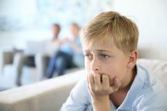 Muchacho del adolescente en casa que se sienta en el sofá referido Imagen de archivo libre de regalías