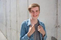 Muchacho del adolescente en dril de algodón azul sobre fondo concreto Imágenes de archivo libres de regalías