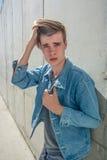 Muchacho del adolescente en dril de algodón azul sobre fondo urbano Fotos de archivo libres de regalías