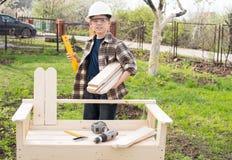 Muchacho del adolescente en el trabajo del casco al aire libre carpintería A constructiva Imagenes de archivo