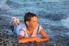 Muchacho del adolescente en la ropa mojada que miente en la costa Imagen de archivo