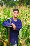 Muchacho del adolescente en los dresss del granjero de Tailandia en el campo de maíz Fotografía de archivo