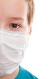 Muchacho del adolescente en máscara quirúrgica Imagenes de archivo