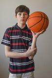 Muchacho del adolescente en una camisa azul marino con las rayas y con una bola para el baloncesto Fotos de archivo libres de regalías
