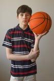 Muchacho del adolescente en una camisa azul marino con las rayas y con una bola para el baloncesto Imagen de archivo libre de regalías
