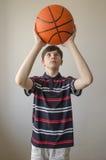 Muchacho del adolescente en una camisa azul marino con las rayas y con una bola para el baloncesto Foto de archivo libre de regalías