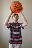 Muchacho del adolescente en una camisa azul marino con las rayas y con una bola para el baloncesto Fotos de archivo