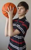 Muchacho del adolescente en una camisa azul marino con las rayas y con una bola para el baloncesto Imagenes de archivo