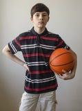 Muchacho del adolescente en una camisa azul marino con las rayas y con una bola para el baloncesto Imágenes de archivo libres de regalías