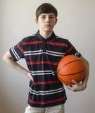 Muchacho del adolescente en una camisa azul marino con las rayas y con una bola para el baloncesto Fotografía de archivo libre de regalías