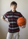 Muchacho del adolescente en una camisa azul marino con las rayas y con una bola para el baloncesto Imagen de archivo
