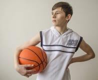Muchacho del adolescente en una camisa blanca con una bola para el baloncesto Imagenes de archivo