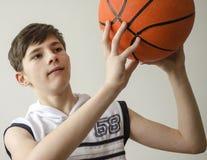 Muchacho del adolescente en una camisa blanca con una bola para el baloncesto Imagen de archivo