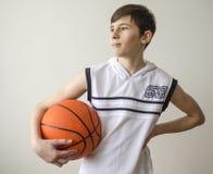 Muchacho del adolescente en una camisa blanca con una bola para el baloncesto Imagen de archivo libre de regalías