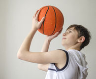 Muchacho del adolescente en una camisa blanca con una bola para el baloncesto Fotos de archivo