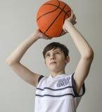 Muchacho del adolescente en una camisa blanca con una bola para el baloncesto Fotos de archivo libres de regalías