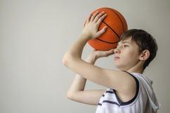 Muchacho del adolescente en una camisa blanca con una bola para el baloncesto Fotografía de archivo libre de regalías