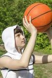 Muchacho del adolescente en una camisa blanca con una bola para el baloncesto Imágenes de archivo libres de regalías