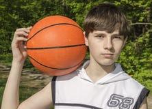 Muchacho del adolescente en una camisa blanca con una bola para el baloncesto Foto de archivo