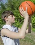 Muchacho del adolescente en una camisa blanca con una bola para el baloncesto Foto de archivo libre de regalías