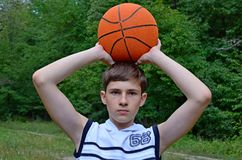 Muchacho del adolescente en una camisa blanca sin las mangas con una bola para el baloncesto Imagenes de archivo