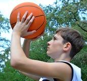 Muchacho del adolescente en una camisa blanca sin las mangas con una bola para el baloncesto Fotos de archivo libres de regalías