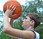 Muchacho del adolescente en una camisa blanca sin las mangas con una bola para el baloncesto Imagen de archivo