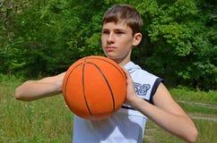 Muchacho del adolescente en una camisa blanca sin las mangas con una bola para el baloncesto Imágenes de archivo libres de regalías