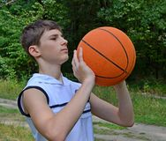 Muchacho del adolescente en una camisa blanca sin las mangas con una bola para el baloncesto Foto de archivo