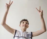 Muchacho del adolescente en una camisa blanca sin las mangas con las manos extendidas en un gesto de la victoria Imagenes de archivo