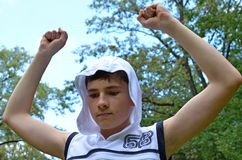 Muchacho del adolescente en una camisa blanca sin las mangas con las manos extendidas en un gesto de la victoria Imágenes de archivo libres de regalías