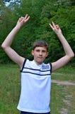 Muchacho del adolescente en una camisa blanca sin las mangas con las manos extendidas en un gesto de la victoria Foto de archivo libre de regalías