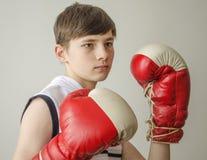 Muchacho del adolescente en una camisa blanca sin las mangas y en guantes de boxeo Fotografía de archivo libre de regalías